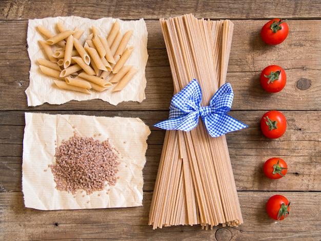 パスタとトマトの木製の背景の上面図