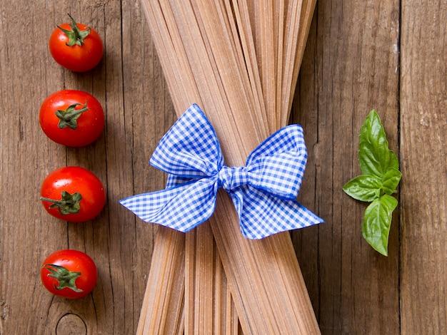 スパゲッティパスタ、トマト、バジルの木製の背景の上面図