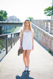 若いハンサムな白人のブロンドのストレート長い髪の女性は、都市でポーズ
