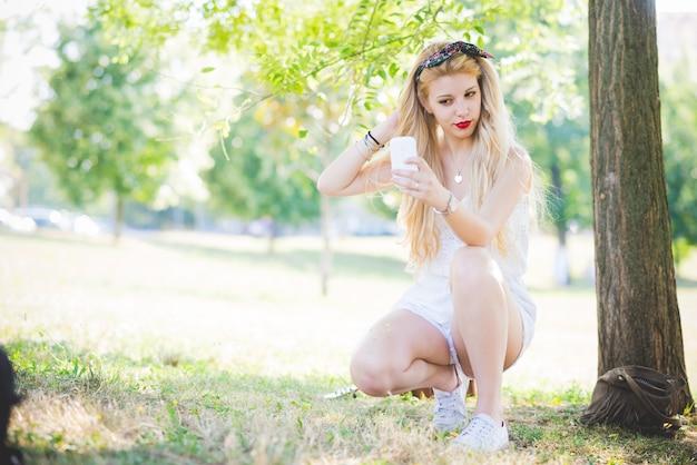 若いハンサムな白人の長いブロンドのストレートヘアの女性は、都市公園にひざまづいた