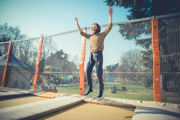 Человек прыгает на батуте на детской площадке