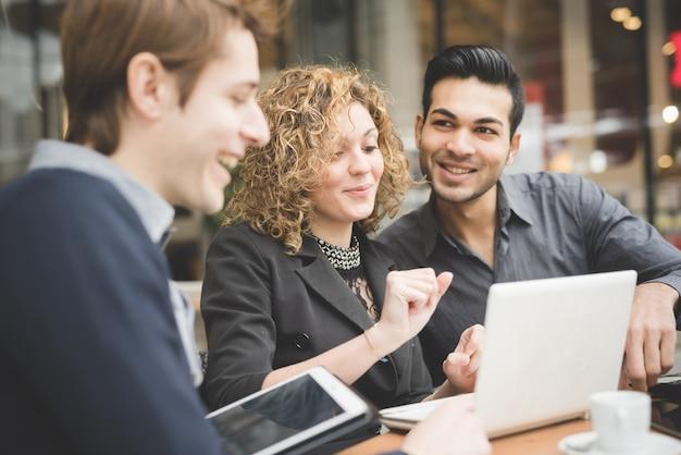 Три молодых многоэтнических современных деловых людей, работающих
