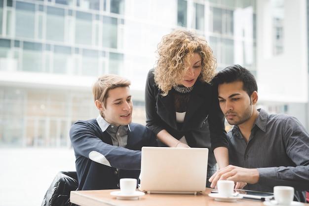 Многорасовые деловые люди, работающие с такими технологическими устройствами, как планшет и ноутбук