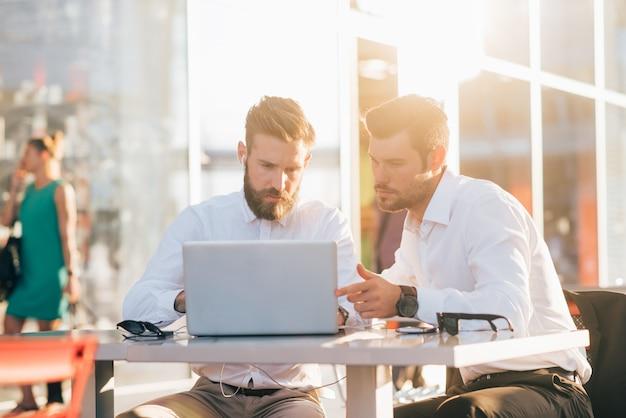 Два молодых современных бизнесмен, используя ноутбук