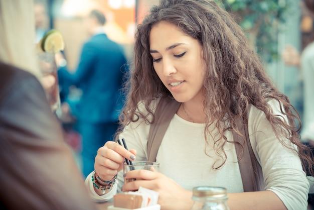 カクテルと美しい縮毛の長いブルネットヘアモロッコの女性
