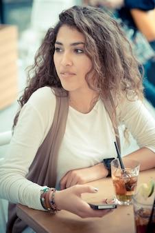 スマートフォンを使用して美しい縮毛の長いブルネットの毛のモロッコの女性