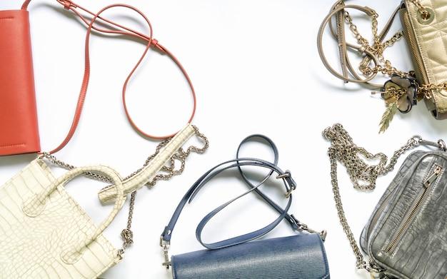 女性のハンドバッグセットのフラットなレイアウト。トレンディなファッション女性の背景。
