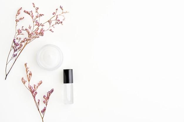 白いクリームのボトルが置かれ、花、モックアップのための空白のラベルパッケージ