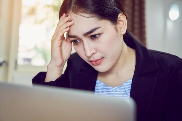 ビジネス女性は座って、コンピュータの画面に長時間疲れを感じます。