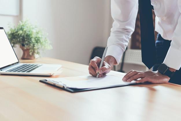 ビジネスマンは彼のオフィスで文書を使って作業し、情報の正確さをチェックします。