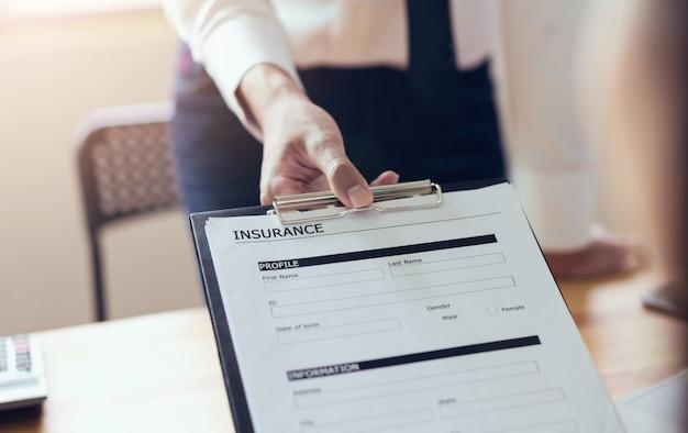 オフィスのビジネスマンは、保険証書を記入します。将来の事故を防止する。