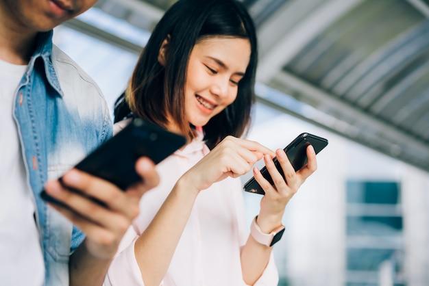 若者たちは、自由な時間に座っている間にスマートフォンを使い、笑顔を浮かべます技術コンセプト