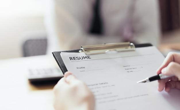 若い女性が求職申請書を確認するために履歴書雇用主を提出します。