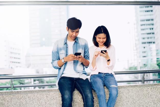 アジアの若者たちは、スマートフォンを使用して、自由時間に座っている間に笑っています。技術コンセプト。