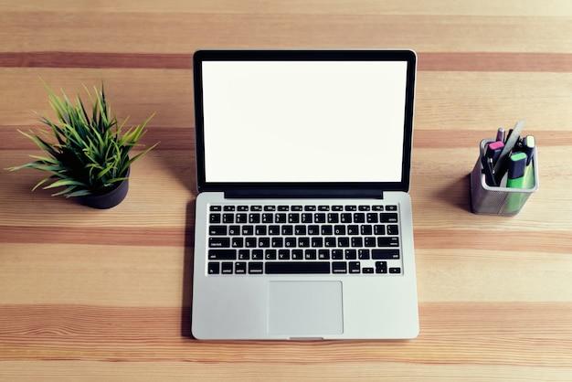 グラフィック表示モンタージュの事務室の背景にテーブルの上のノートパソコン。