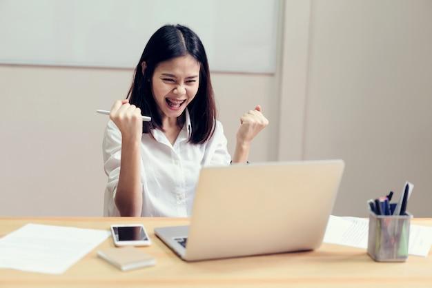 ビジネスウーマンは仕事で成功して、幸せなバックグラウンドでテーブルの上に文書を見せて幸せです。