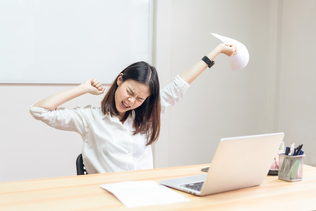 女性はコンピュータのために背中の痛みがあり、長い間働いています。