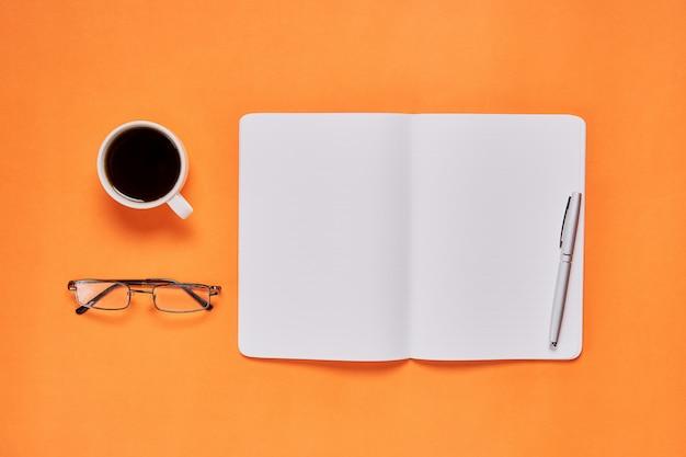 黒い画面のノートブックの空白とペンの背景を配置しました。広告に使用されるグラフィックに適しています。