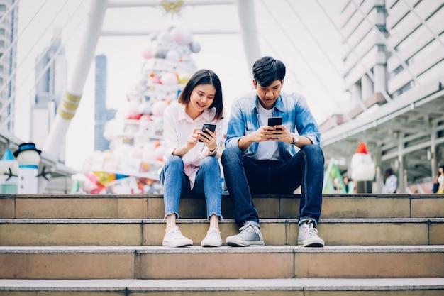 Молодые люди используют смартфон и улыбаются сидя на свободном времени.