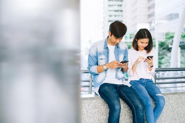 Азиатские молодые люди используют смартфон и улыбаются сидя на свободное время.
