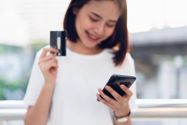 クレジットカードを保持している女性がオンラインで支払い、ウェブサイトを通して店のためのスマートフォンを使用して。便利なオンラインショッピングの概念
