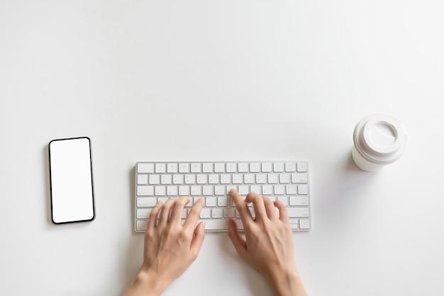 女性の手がキーボードとスマートフォン、机の上のコーヒーカップを入力しています。