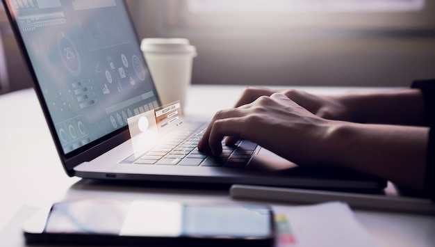 テーブルの背景にオフィスで働く上でキーボードのラップトップとアカウントのログイン画面を入力する女性。インターネット利用に関する安全性の概念