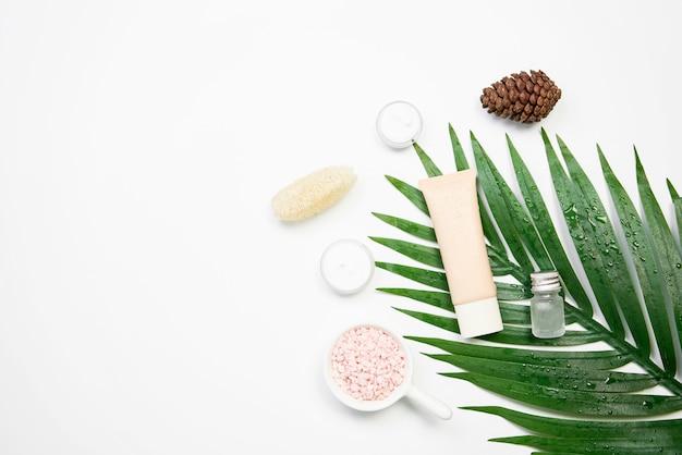 Макет косметический крем бутылки, пустой ярлык пакета и ингредиенты на фоне зеленых листьев.