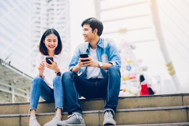 若い人たちは、スマートフォンを使用し、自由な時間に座っている間に微笑んでいます。技術コンセプト