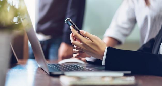 ビジネスの女性がオフィスで携帯電話を使用して、スマートフォンを保持しています。
