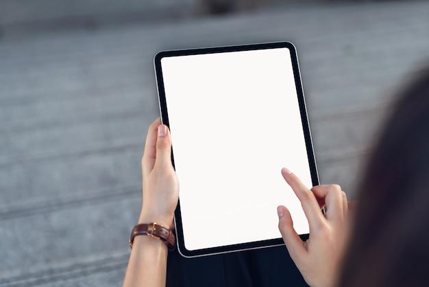 分離の空白のタブレット画面を持っている手。あなたのスクリーンを使って広告を出しましょう。