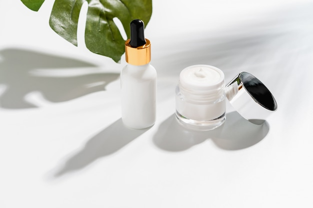 白いセラムボトルとクリームジャー、美容製品ブランドのモックアップ。白い背景の上の平面図です。