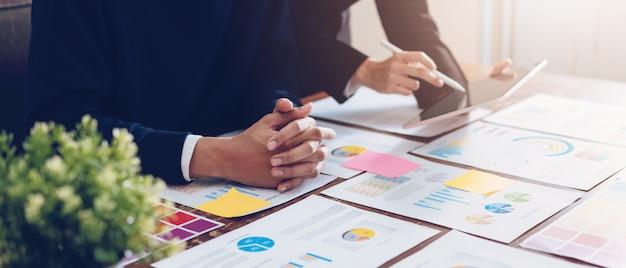 タブレットを使用してオフィスのテーブルと財務書類に取り組んでいる事業チーム。