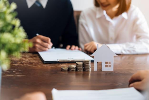 カップルはブローカーから家を買うために契約に署名しました。
