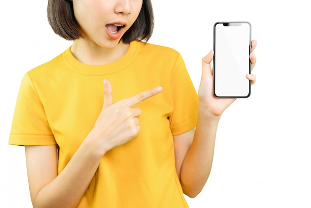 成功に驚いたとスマートフォンを手と指で指している幸せな笑顔の女性。
