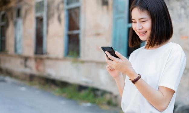 幸せな笑顔とスマートフォンを使用してのアジアの女性。