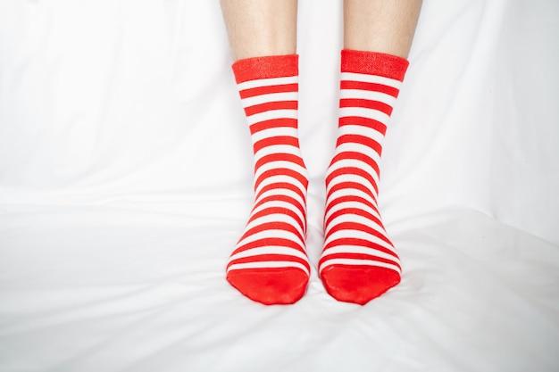 Женские ножки в чулках чередуются, боковая стойка на белом тканевом полу.