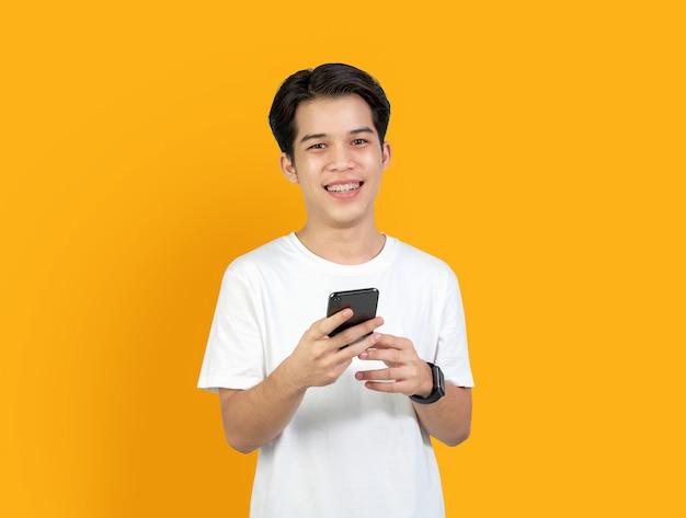Молодой усмехаясь азиатский человек с держать умный телефон на апельсине