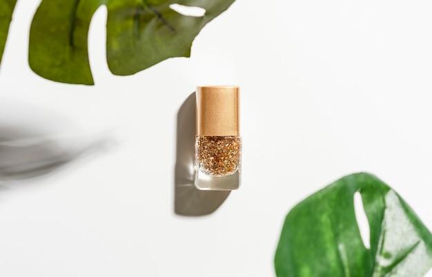 Лак для ногтей красивых золотых цветов на белом.