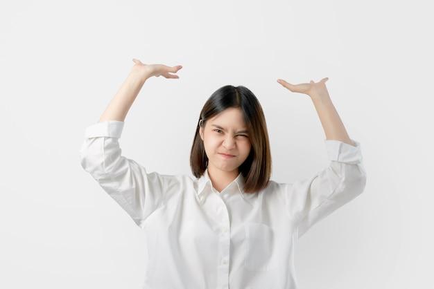 白いカジュアルな服装の若いアジア女性は上から重いものを保持しようとします。
