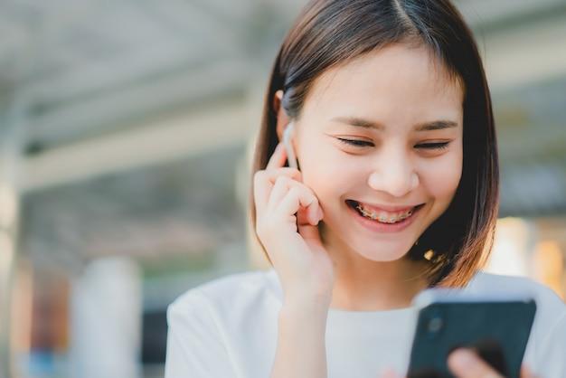 アジアの女性は笑みを浮かべて、白いヘッドフォンから音楽を聴きます。