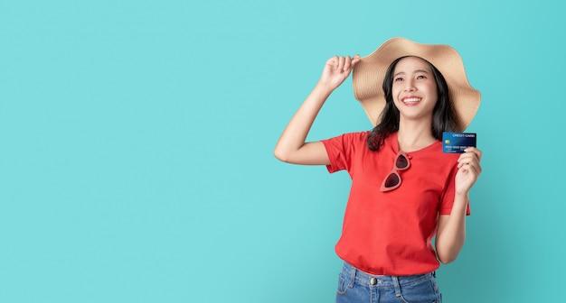 Улыбка счастливо азиатская женщина держа кредитную карточку и смотря вперед на голубой предпосылке с космосом экземпляра.