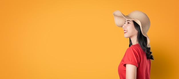 コピースペースとオレンジ色の背景に直面して立っていると楽しみにして笑顔で立っている美しいアジアの女性。