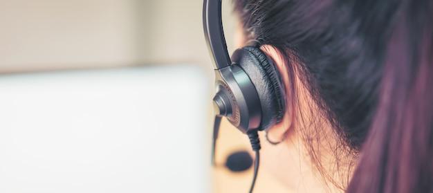 職場でのカスタマーサポート電話オペレーターのマイクヘッドセットを着ている女性コンサルタントの背面図。