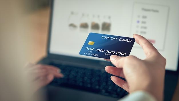 クレジットカードとプレスのラップトップコンピューターを持つ女性の手は、製品の支払いコードを入力します。