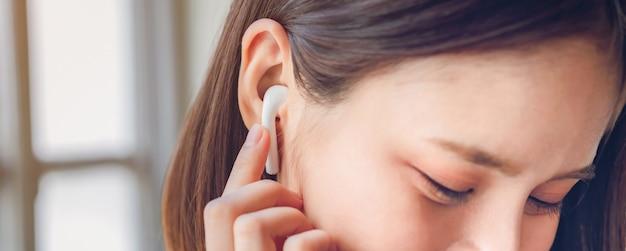 女性は白いヘッドフォンから音楽を聴いています。