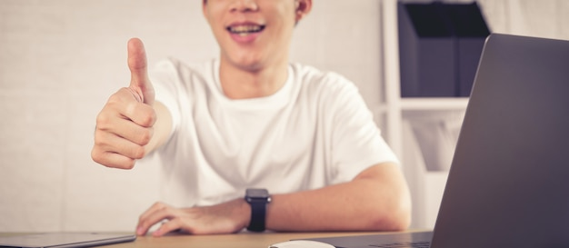 男の顔を笑顔で親指を表示またはオフィスの机の上に座って、ビジネスの成功のような。