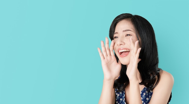 口に手で発表し、秘密を告げる魅力的な若いアジアの女性。