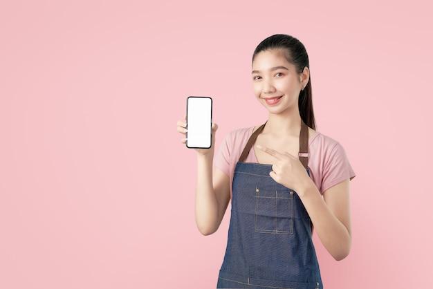 若い笑顔のアジア女性は、人差し指でスマートフォンの空白の画面を表示します。