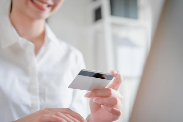オンラインショッピングとクレジットカードを保持しているアジアの女性を幸せに笑顔します。